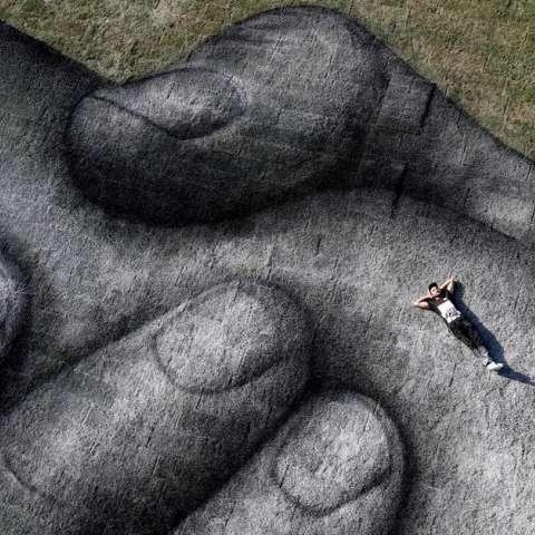 El artista franco-suizo Saype posa en su propia pintura biodegradable titulada 'detrás de los proyectos del muro' en un espacio flotante en el estrecho del Bósforo en Estambul, Turquía.