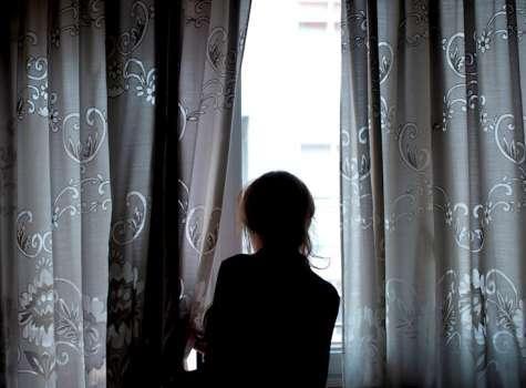 Una mujer observa a través de la ventana de su vivienda, en foto de archivo. EFE