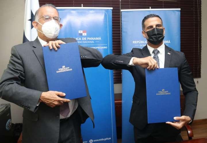 Ambos funcionarios firman el acuerdo.