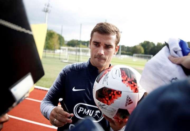 El jugador de la selección nacional de fútbol francesa, Antoine Griezmann, firma autógrafos luego del entrenamiento de su selección./EFE
