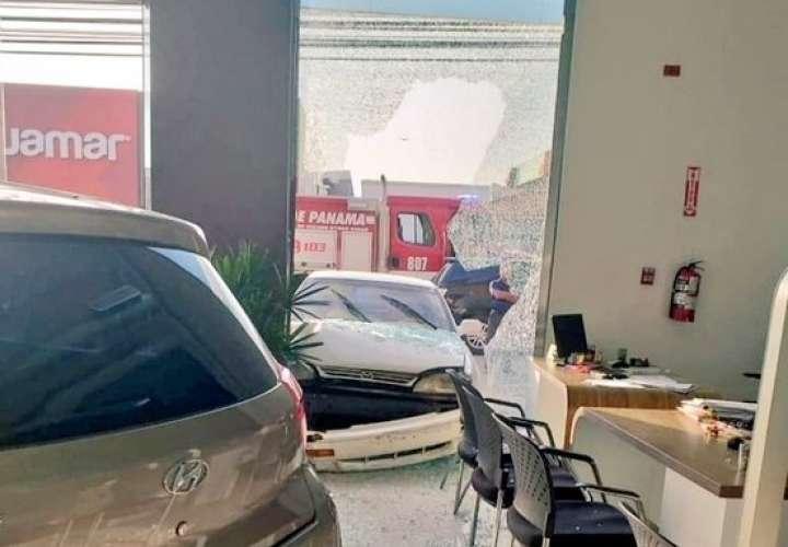 Colisión entre dos autos, uno termina estrellado contra vidriera de local