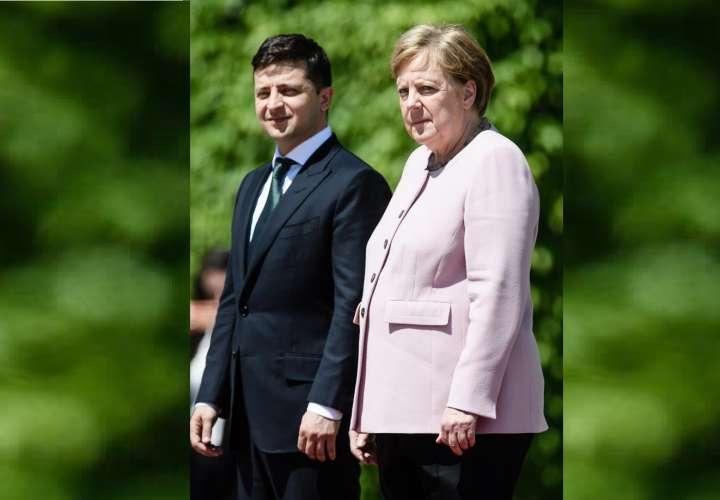 La canciller alemana, Angela Merkel (d), y el presidente de Ucrania, Volodymyr Zelensky, durante la ceremonia de bienvenida con honores militares celebrada este martes, en Berlín (Alemania). EFE