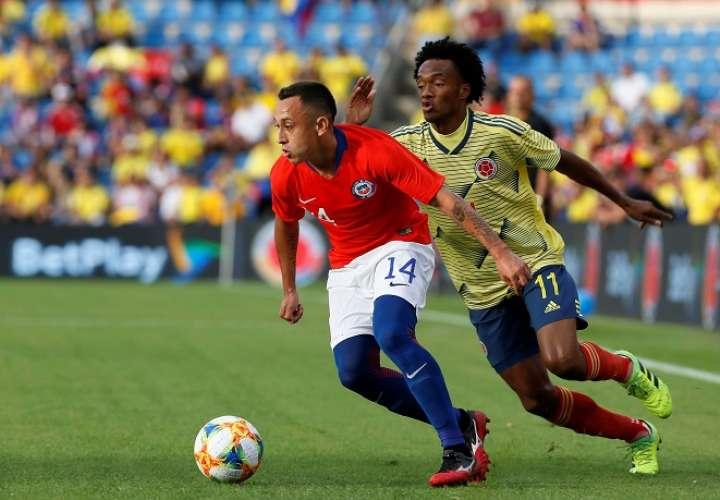 El centrocampista de Chile Fabián Orellana (i) controla el balón ante el centrocampista de Colombia Juan Guillermo Cuadrado. Foto: EFE