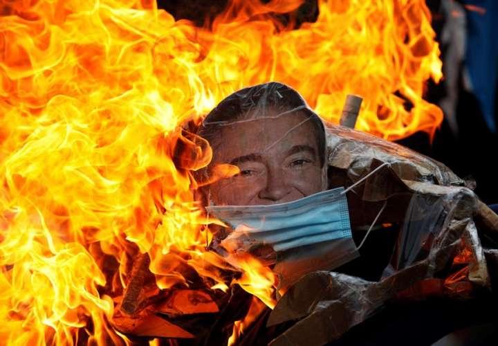 Un muñeco con la imagen del presidente de Panamá, Laurentino Cortizo es quemado durante una protesta