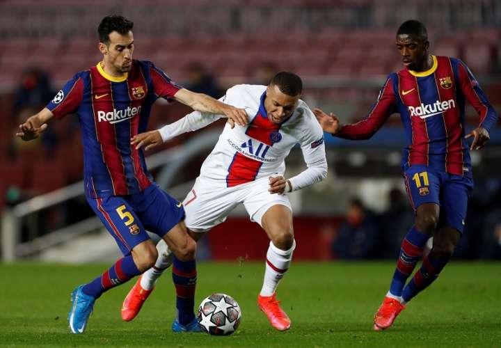 Busquets (i) y Dembélé (d) disputan un balón ante Mbappé (c)./EFE