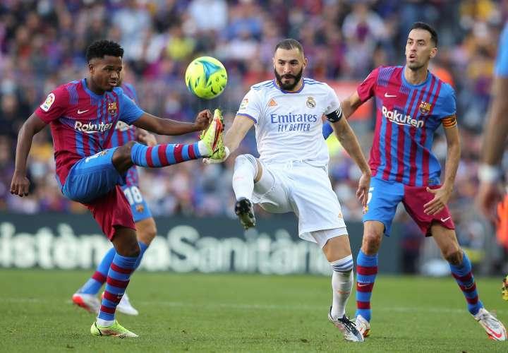 El delantero del Real Madrid Karim Benzema (c) y los jugadores del FC Barcelona Ansu Fati (i) y Sergio Busquets. /EFE