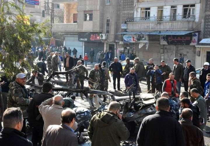 Varios curiosos rodean varios vehículos destruidos tras la explosión de un microbús en la ciudad de Homs (Siria) este 5 de diciembre. EFE