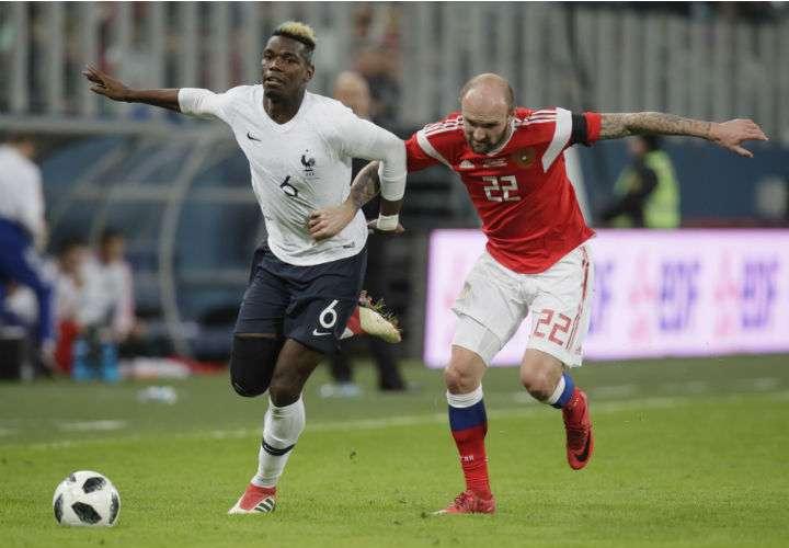 El francés Paul Pogbá (izq.) y el ruso Konstantin Rausch disputan el balón en el duelo amistoso. Foto AP
