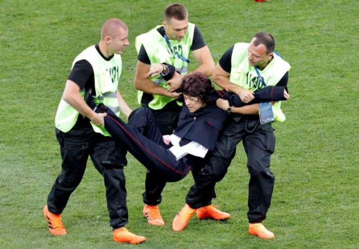 Miembros de seguridad reducen a un espontáneo que saltó al campo durante el partido Francia-Croacia. Foto:EFE