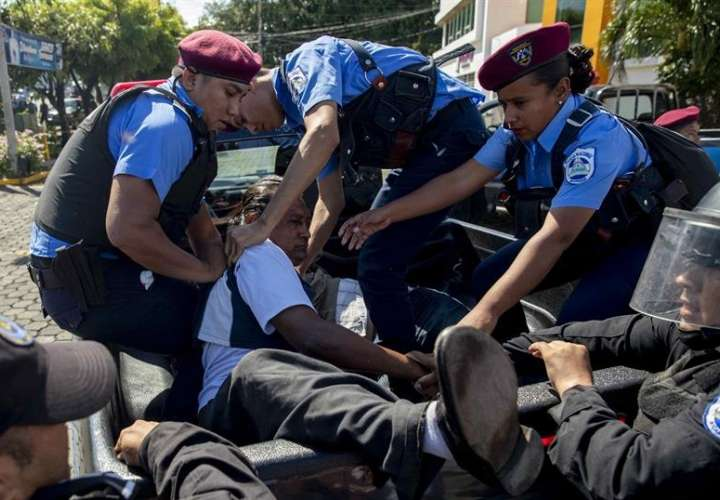 Policías detienen a un manifestante durante la marcha