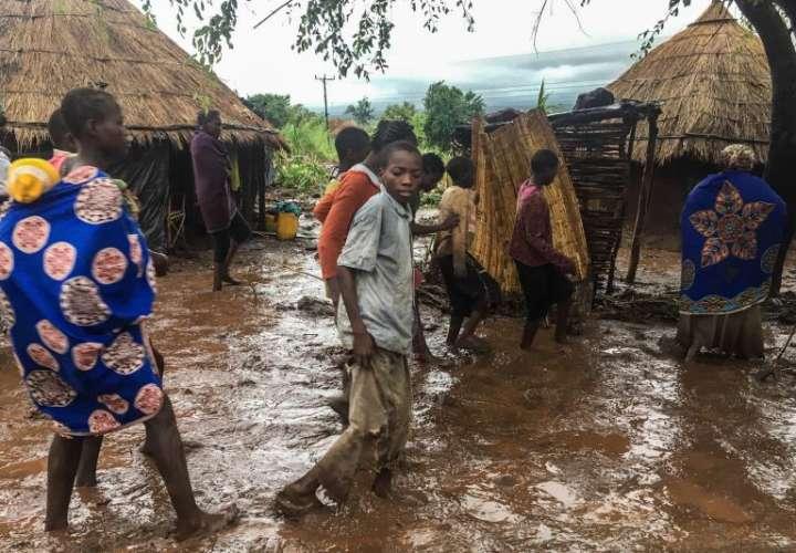 Habitantes de Chiluvi, una aldea del centro de Mozambique, caminan por una calle cubierta de lodo tras el paso del ciclón Idai, este lunes. EFE