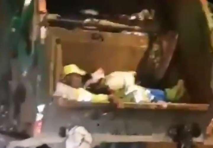 Dormía plácidamente en la 'chuta' del camión de basura  [Video]