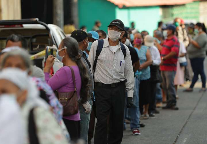 Salvadoreños abarrotan los bancos para cobrar bono estatal alimenticio