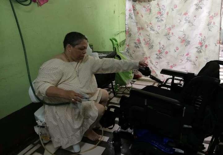 La hermana Ana Fisher mientras desinfecta la silla de ruedas en el baño improvisado fuera de su casa. Imagen: Cortesía