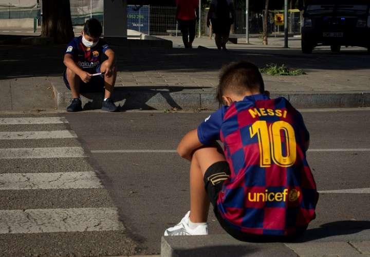 -Dos jóvenes aficionado esperan a la entrada de la ciudad deportiva Joan Gamper en Barcelona las llegada de los jugadores. /EFE