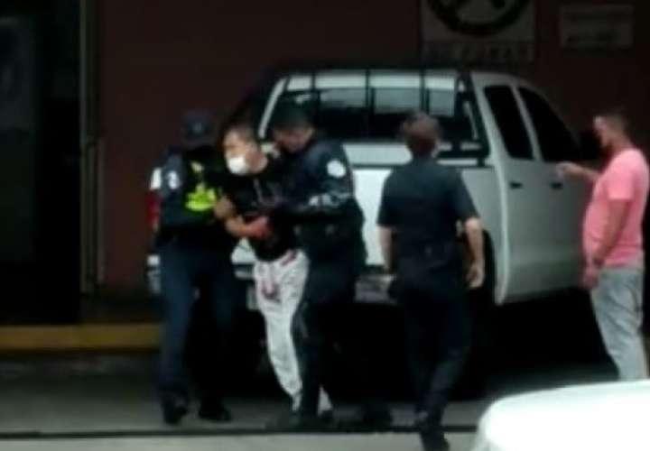 Unidades de la Policía Nacional ayudan al herido a descender del vehículo a su llegada al Hospital Santo Tomás.