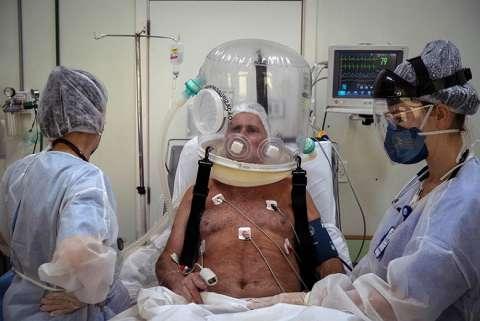 Trabajadores de la salud atienden con un casco burbuja a un paciente con la covid-19 hoy en la ciudad de Sao Leopoldo (Brasil). EF