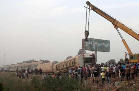 Una grúa levanta un vagón dañado de un tren de pasajeros que se descarriló en El Cairo. FOTO/EFE