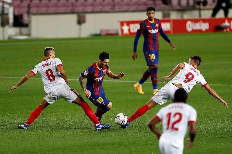 Messi (c) intenta escaparse de Joan Jordan (i) y de Luuk de Jong (d), del Sevilla. /EFE
