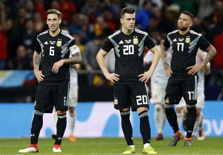 Los jugadores argentinos Lucas Biglia, Giovani Lo Celso y Nicolás Otamendi no pudieron evitar la goleada de España. Foto AP
