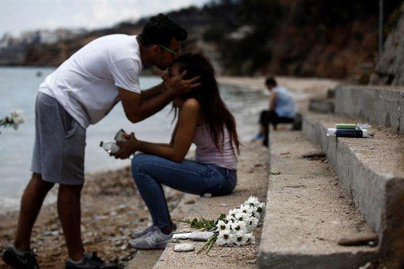 Un hombre besa a su hermana mientras un ramo de flores yace en el lugar donde un bebé de seis meses perdió la vida tras el incendio forestal de Mati, al noreste de Atenas (Grecia).  EFE