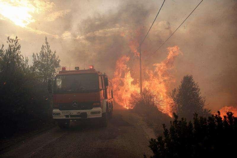 Bomberos tratan de extinguir un incendio en Penteli, al norte de Atenas (Grecia), hoy. EFE