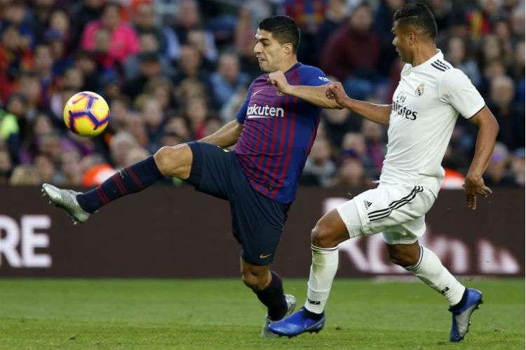 Casemiro (der.) trata de defender a Luis Suárez. Foto: EFE