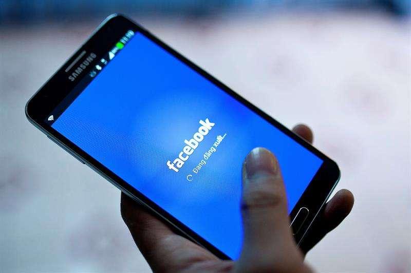 Imagen de archivo que muestra a una persona mientras inicia la red social Facebook en un teléfono móvil. EFE/Archivo