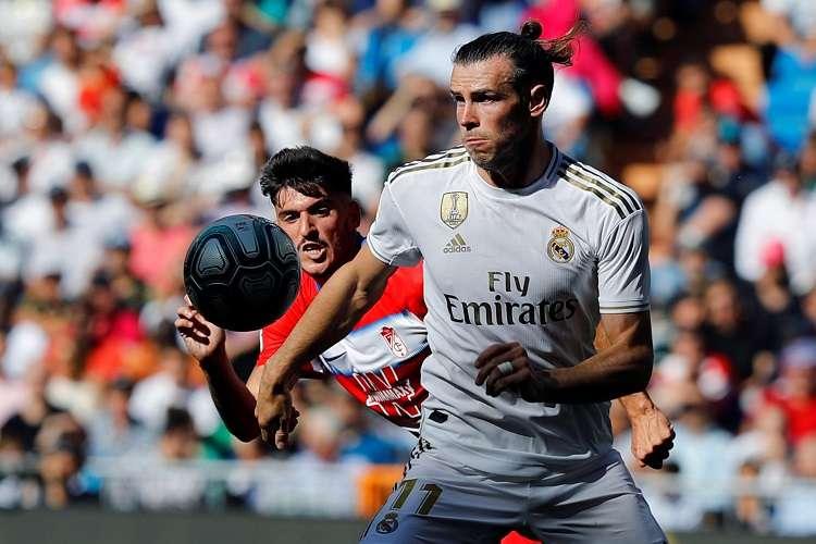 El jugador galés del Real Madrid, Gareth Bale (d), disputa el balón con el jugador del Granada Carlos Neva (i),. Foto: AP