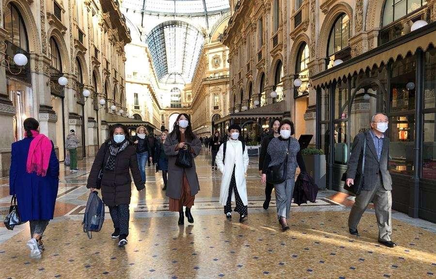 Las personas asiáticas con máscaras protectoras caminan en una Galleria Vittorio Emanuele inusualmente despoblada, en Milán, norte de Italia, el 24 de febrero de 2020.  EFE