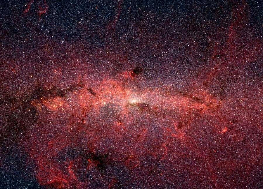 Imagen del centro de la galaxia obtenida con el telescopio espacial Spitzer, donde se pueden ver zonas de nubes moleculares. EFE