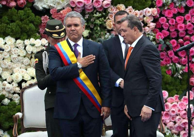 El presidente del Senado, Ernesto Macías (d), le impone la banda presidencial al nuevo presidente colombiano, Iván Duque Márquez (c-i), durante la ceremonia de investidura hoy, martes 7 de agosto de 2018, en la Plaza de Bolívar de Bogotá (Colombia). EFE
