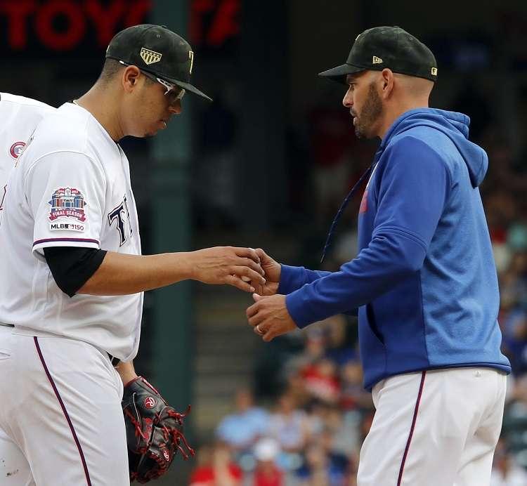 Ariel Jurado (izq.) junto a Chris Woodward, técnico de los Rangers. / Foto AP