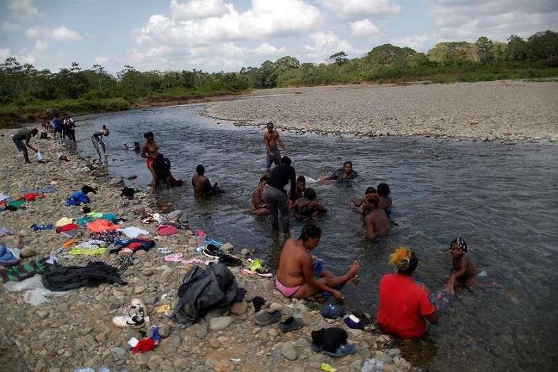 Migrantes haitianos se bañan en el río Tuquesa, en la comunidad de Bajo Chiquito, en Darién (Panamá). EFE/