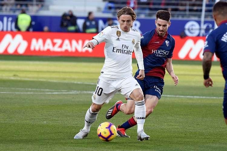 El delantero croata del Real Madrid Luka Modric (i) y el cenrocampista del Huesca Moisés Gómez. Foto: EFE