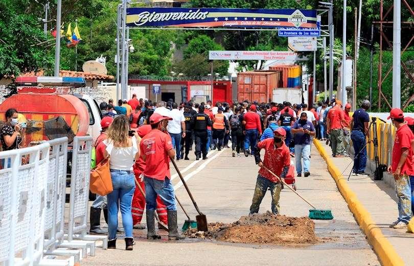 Trabajadores limpian tras el desmonte de un contenedor que impide el paso fronterizo entre Colombia y Venezuela, luego del anuncio de reapertura hoy. EFE