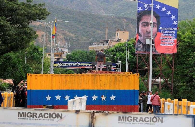 Autoridades caminan junto a uno de los contenedores que impiden el paso fronteriza entre Colombia y Venezuela, hoy, en el puente internacional Simón Bolívar, en San Antonio del Táchira (Venezuela). EFE