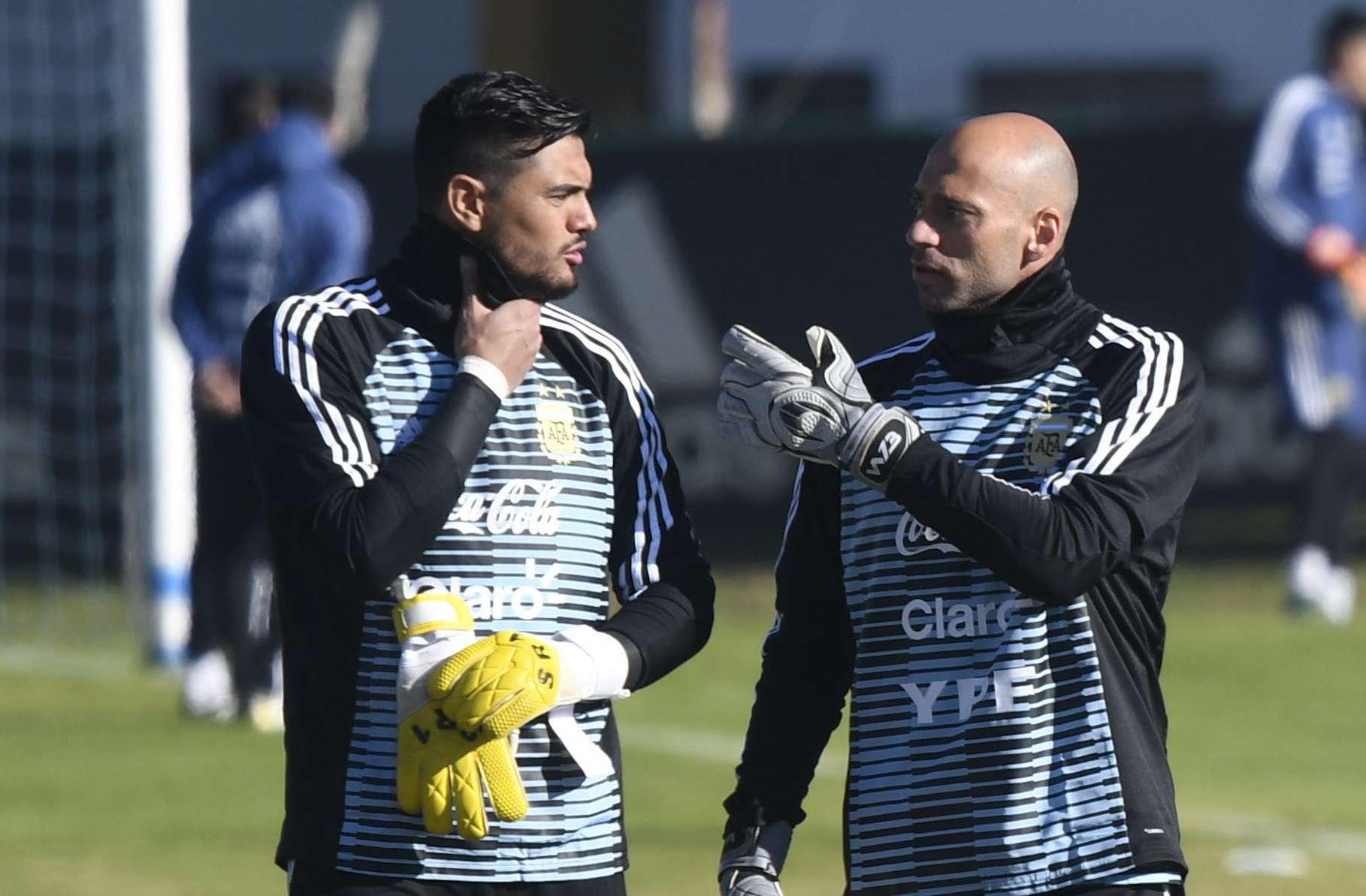 Sergio Romero (izq.) conversa con su compañero Wilfredo Caballero./ AP
