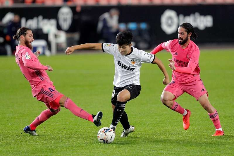 El jugador del Valencia CF, Kang In entre Sergio Ramos (i) e Isco (d) , del Real Madrid. /EFE